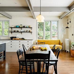 ポートランドのヴィクトリアン調のおしゃれなダイニングキッチン (エプロンフロントシンク、シェーカースタイル扉のキャビネット、グレーのキャビネット、大理石カウンター、白いキッチンパネル、サブウェイタイルのキッチンパネル) の写真