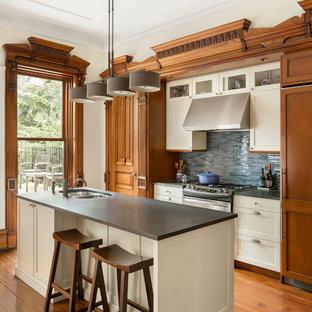 Klassische Küche mit Doppelwaschbecken, Schrankfronten im Shaker-Stil, beigen Schränken, Küchenrückwand in Blau, Rückwand aus Stäbchenfliesen, Elektrogeräten mit Frontblende, braunem Holzboden, Kücheninsel und grauer Arbeitsplatte in New York