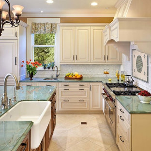 Photo of an expansive victorian u-shaped eat-in kitchen in San Francisco with raised-panel cabinets, white cabinets, quartzite benchtops, white splashback, stone tile splashback, panelled appliances, porcelain floors, with island and a farmhouse sink.