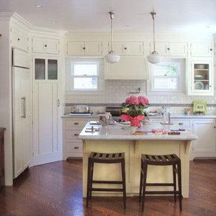 サンフランシスコの中サイズのヴィクトリアン調のおしゃれなキッチン (シェーカースタイル扉のキャビネット、白いキャビネット、クオーツストーンカウンター、白いキッチンパネル、サブウェイタイルのキッチンパネル、パネルと同色の調理設備、無垢フローリング) の写真