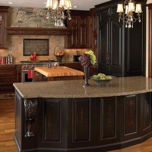 Cette photo montre une grande cuisine américaine victorienne en L avec un placard avec porte à panneau surélevé, des portes de placard en bois sombre, un plan de travail en quartz modifié, une crédence beige, une crédence en carrelage de pierre, un îlot central, un évier de ferme, un électroménager en acier inoxydable, un sol en bois brun et un plan de travail marron.