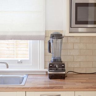 ロンドンの小さいインダストリアルスタイルのおしゃれなキッチン (シングルシンク、シェーカースタイル扉のキャビネット、ベージュのキャビネット、木材カウンター、ベージュキッチンパネル、セラミックタイルのキッチンパネル、シルバーの調理設備、淡色無垢フローリング、アイランドなし) の写真
