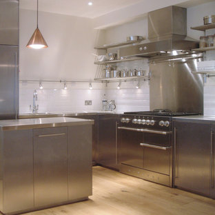 Inspiration for a mid-sized contemporary l-shaped open plan kitchen in London with an integrated sink, flat-panel cabinets, stainless steel cabinets, stainless steel benchtops, white splashback, cement tile splashback, stainless steel appliances, light hardwood floors, with island and beige floor.