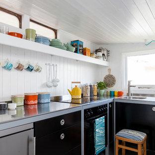 Ejemplo de cocina en L, escandinava, con armarios con paneles lisos, puertas de armario negras y electrodomésticos de acero inoxidable