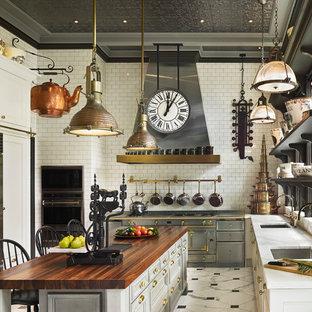 フィラデルフィアの大きいヴィクトリアン調のおしゃれなキッチン (アンダーカウンターシンク、白いキャビネット、木材カウンター、白いキッチンパネル、サブウェイタイルのキッチンパネル、シルバーの調理設備の、大理石の床、落し込みパネル扉のキャビネット) の写真