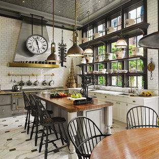 Неиссякаемый источник вдохновения для домашнего уюта: большая п-образная кухня-гостиная в викторианском стиле с врезной раковиной, белыми фасадами, мраморной столешницей, белым фартуком, фартуком из плитки кабанчик, техникой из нержавеющей стали, мраморным полом и островом