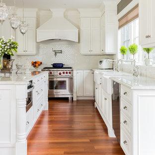 ボストンの大きいヴィクトリアン調のおしゃれなアイランドキッチン (エプロンフロントシンク、白いキャビネット、珪岩カウンター、白いキッチンパネル、シルバーの調理設備、無垢フローリング、落し込みパネル扉のキャビネット) の写真
