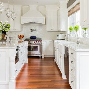 Large victorian kitchen designs - Large ornate medium tone wood floor kitchen photo in Boston with a farmhouse sink, white cabinets, quartzite countertops, white backsplash, stainless steel appliances, an island and recessed-panel cabinets