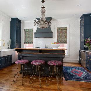 デンバーのヴィクトリアン調のおしゃれなキッチン (エプロンフロントシンク、レイズドパネル扉のキャビネット、青いキャビネット、白いキッチンパネル、サブウェイタイルのキッチンパネル、シルバーの調理設備の、無垢フローリング、茶色い床、白いキッチンカウンター) の写真