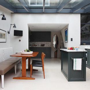 Cette image montre une cuisine américaine linéaire design de taille moyenne avec un évier posé, un placard à porte shaker, des portes de placards vertess, un plan de travail en marbre, une crédence en marbre, un électroménager en acier inoxydable, un sol en calcaire et un îlot central.