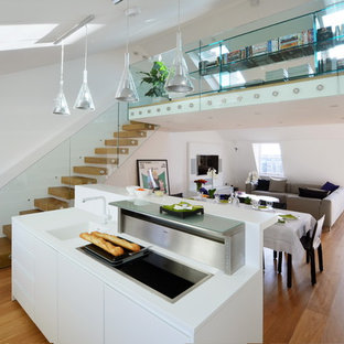 Photo of a medium sized contemporary open plan kitchen in London with a built-in sink, flat-panel cabinets, white cabinets, composite countertops, white splashback, stainless steel appliances, an island, white worktops, light hardwood flooring and beige floors.