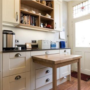 Esempio di una cucina ad U vittoriana chiusa e di medie dimensioni con lavello stile country, ante in stile shaker, ante bianche, top in vetro riciclato, paraspruzzi bianco, paraspruzzi con lastra di vetro, elettrodomestici bianchi, pavimento in legno massello medio e nessuna isola