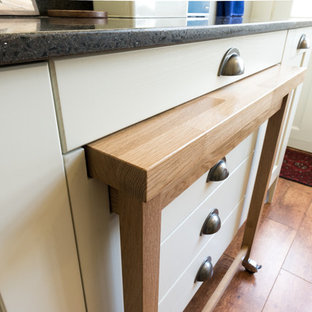 Mid-sized victorian u-shaped separate kitchen in Other with a farmhouse sink, shaker cabinets, white cabinets, recycled glass benchtops, white splashback, glass sheet splashback, white appliances, medium hardwood floors and no island.