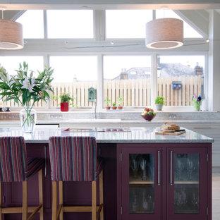 Imagen de cocina de galera, campestre, con fregadero encastrado, armarios tipo vitrina, puertas de armario violetas, salpicadero verde, una isla y suelo beige