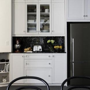モントリオールの小さいヴィクトリアン調のおしゃれな独立型キッチン (シングルシンク、白いキャビネット、御影石カウンター、黒いキッチンパネル、石タイルのキッチンパネル、シルバーの調理設備の、カーペット敷き、アイランドなし) の写真