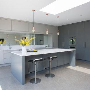 Ispirazione per un cucina con isola centrale minimal di medie dimensioni con ante lisce, ante grigie, paraspruzzi a specchio, lavello sottopiano, pavimento grigio e pavimento in gres porcellanato
