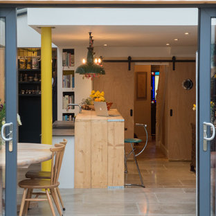 Inspiration for a contemporary galley open plan kitchen in Devon with flat-panel cabinets, white cabinets, engineered stone countertops, grey splashback, integrated appliances, limestone flooring, a breakfast bar, brown floors, a double-bowl sink and multicoloured worktops.
