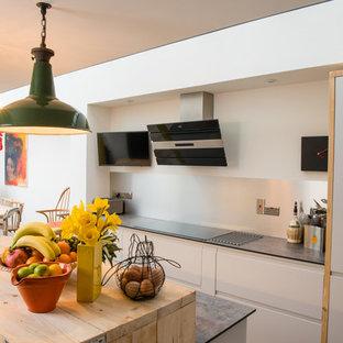 Idee per una cucina minimal di medie dimensioni con ante lisce, ante bianche, top in legno, paraspruzzi a effetto metallico, elettrodomestici in acciaio inossidabile, pavimento in pietra calcarea, isola, paraspruzzi con piastrelle di metallo, pavimento beige e top multicolore