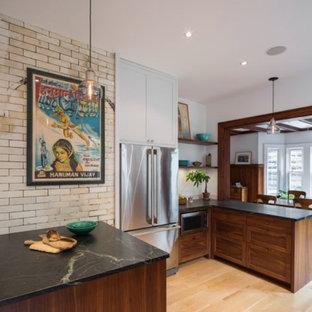ニューヨークの中サイズのインダストリアルスタイルのおしゃれなキッチン (アンダーカウンターシンク、シェーカースタイル扉のキャビネット、濃色木目調キャビネット、ソープストーンカウンター、白いキッチンパネル、石スラブのキッチンパネル、シルバーの調理設備の、淡色無垢フローリング、ベージュの床) の写真