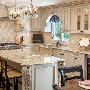 Photo of an expansive victorian u-shaped kitchen/diner in New York with recessed-panel cabinets, beige cabinets, granite worktops, an island, a belfast sink, beige splashback, metro tiled splashback, stainless steel appliances, medium hardwood flooring, brown floors and beige worktops.