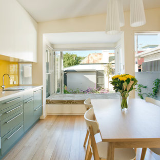 This is an example of a small contemporary single-wall eat-in kitchen in Sydney with flat-panel cabinets, stainless steel appliances, yellow splashback, glass sheet splashback, green cabinets, a single-bowl sink, light hardwood floors and no island.