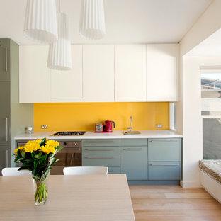 Einzeilige, Kleine Moderne Wohnküche ohne Insel mit flächenbündigen Schrankfronten, Küchengeräten aus Edelstahl, Küchenrückwand in Gelb, grünen Schränken, Waschbecken, Glasrückwand und hellem Holzboden in Sydney