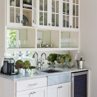 This is an example of a mid-sized arts and crafts galley eat-in kitchen in Minneapolis with an undermount sink, glass-front cabinets, white cabinets, marble benchtops, mirror splashback, light hardwood floors and with island.