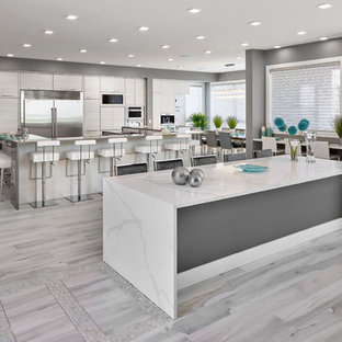 Design ideas for a large contemporary u-shaped eat-in kitchen in Edmonton with an undermount sink, louvered cabinets, grey cabinets, quartz benchtops, stainless steel appliances, porcelain floors, multiple islands, grey floor and white benchtop.