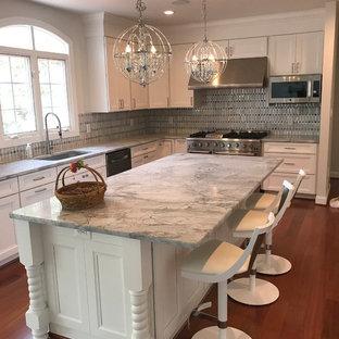 ワシントンD.C.の中サイズのトラディショナルスタイルのおしゃれなキッチン (アンダーカウンターシンク、落し込みパネル扉のキャビネット、白いキャビネット、御影石カウンター、グレーのキッチンパネル、シルバーの調理設備の、濃色無垢フローリング、赤い床、グレーのキッチンカウンター) の写真