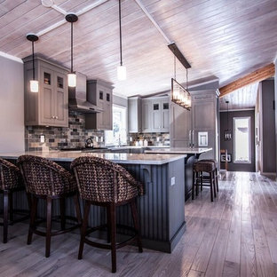 Mid-sized transitional u-shaped eat-in kitchen in Chicago with a farmhouse sink, flat-panel cabinets, green cabinets, quartzite benchtops, multi-coloured splashback, stone tile splashback, panelled appliances, light hardwood floors and with island.