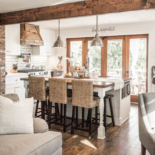 Cottage chic single-wall dark wood floor and brown floor kitchen photo in Orange County with an undermount sink, shaker cabinets, white cabinets, white backsplash, subway tile backsplash, stainless steel appliances, an island and white countertops
