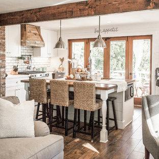 オレンジカウンティのシャビーシック調のおしゃれなキッチン (アンダーカウンターシンク、シェーカースタイル扉のキャビネット、白いキャビネット、白いキッチンパネル、サブウェイタイルのキッチンパネル、シルバーの調理設備の、濃色無垢フローリング、茶色い床、白いキッチンカウンター) の写真