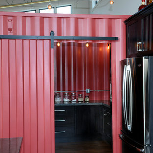 Inspiration for a mid-sized industrial single-wall open plan kitchen in Other with black cabinets, black splashback, stainless steel appliances, with island, recessed-panel cabinets, concrete benchtops, ceramic splashback and medium hardwood floors.
