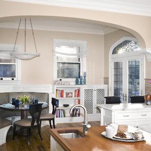 ニューヨークの大きいトラディショナルスタイルのおしゃれなキッチン (大理石カウンター、アンダーカウンターシンク、落し込みパネル扉のキャビネット、白いキャビネット、ベージュキッチンパネル、サブウェイタイルのキッチンパネル、シルバーの調理設備の、無垢フローリング、茶色い床、グレーのキッチンカウンター) の写真