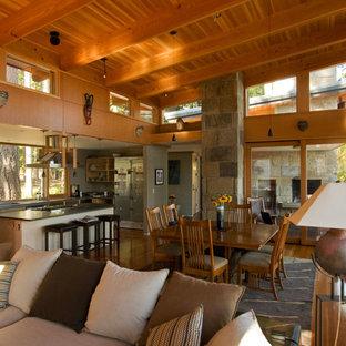 Immagine di una grande cucina rustica con lavello sottopiano, ante lisce, ante in legno chiaro, top in cemento, parquet scuro, isola e pavimento marrone