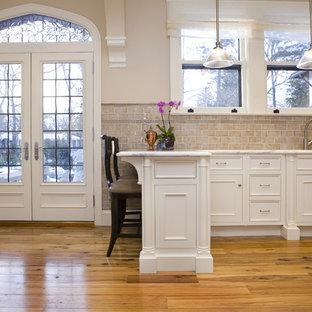 Große Klassische Wohnküche mit Schrankfronten mit vertiefter Füllung, weißen Schränken, Küchenrückwand in Beige, Rückwand aus Metrofliesen, Küchengeräten aus Edelstahl, Marmor-Arbeitsplatte, Halbinsel, Unterbauwaschbecken, hellem Holzboden, beigem Boden und grauer Arbeitsplatte in New York