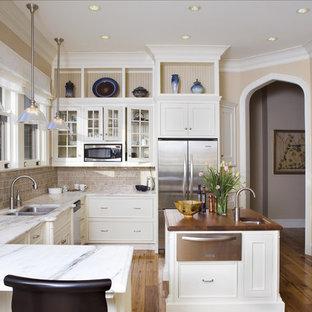 Geschlossene, Große Klassische Küche in U-Form mit Glasfronten, Küchengeräten aus Edelstahl, Marmor-Arbeitsplatte, Doppelwaschbecken, weißen Schränken, Küchenrückwand in Beige, Rückwand aus Metrofliesen, braunem Holzboden, Kücheninsel, braunem Boden und grauer Arbeitsplatte in New York