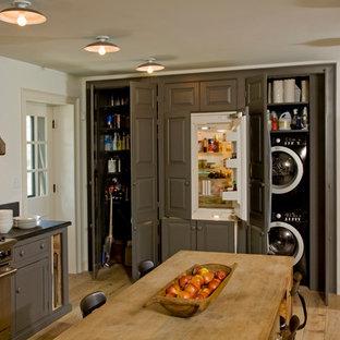 Immagine di un'ampia cucina country chiusa con ante a filo, ante grigie, top in granito, paraspruzzi nero, elettrodomestici in acciaio inossidabile e parquet chiaro