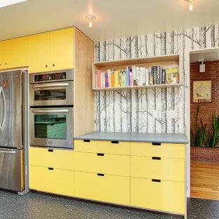シアトルのコンテンポラリースタイルのおしゃれなキッチン (フラットパネル扉のキャビネット、黄色いキャビネット、シルバーの調理設備の) の写真