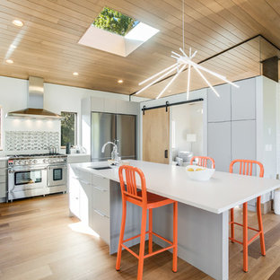Large contemporary u-shaped open plan kitchen in Seattle with flat-panel cabinets, grey cabinets, metallic splashback, stainless steel appliances, light hardwood floors, with island, brown floor, an undermount sink, quartz benchtops and porcelain splashback.