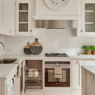 This is an example of a mid-sized country kitchen in Melbourne with an undermount sink, white cabinets, marble benchtops, white splashback, stainless steel appliances, light hardwood floors, with island, glass-front cabinets and subway tile splashback.