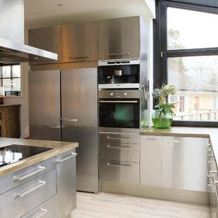 Immagine di una cucina a L industriale chiusa con ante lisce, ante in acciaio inossidabile, top in cemento, elettrodomestici in acciaio inossidabile, parquet chiaro e isola