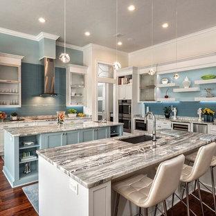 Große Klassische Wohnküche in L-Form mit Unterbauwaschbecken, Schrankfronten im Shaker-Stil, weißen Schränken, Marmor-Arbeitsplatte, Küchenrückwand in Blau, Rückwand aus Metrofliesen, Küchengeräten aus Edelstahl, braunem Holzboden und zwei Kücheninseln in Miami