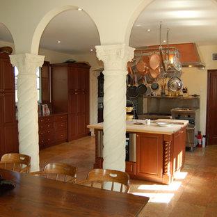 Geschlossene, Große Mediterrane Küche in U-Form mit Unterbauwaschbecken, profilierten Schrankfronten, dunklen Holzschränken, Kupfer-Arbeitsplatte, Küchenrückwand in Metallic, Rückwand aus Metallfliesen, Küchengeräten aus Edelstahl, Schieferboden, Kücheninsel, beigem Boden und brauner Arbeitsplatte in Miami