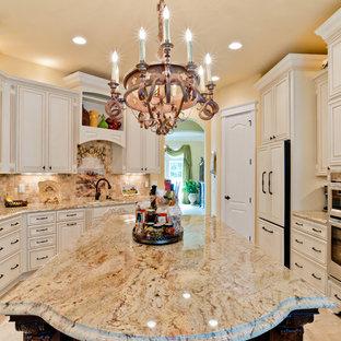 Medelhavsstil inredning av ett stort kök, med en undermonterad diskho, luckor med upphöjd panel, vita skåp, granitbänkskiva, beige stänkskydd, stänkskydd i porslinskakel, rostfria vitvaror, klinkergolv i porslin och en köksö
