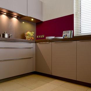 Modelo de cocina en L, moderna, de tamaño medio, abierta, con fregadero integrado, armarios con paneles lisos, puertas de armario marrones, encimera de cuarcita, electrodomésticos con paneles, suelo de baldosas de porcelana, suelo amarillo y encimeras marrones