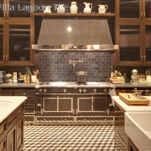 Einzeilige, Geräumige Klassische Küche mit Landhausspüle, Marmor-Arbeitsplatte, Küchenrückwand in Schwarz, Rückwand aus Schiefer, schwarzen Elektrogeräten, Zementfliesen, zwei Kücheninseln, buntem Boden, Glasfronten und dunklen Holzschränken in Los Angeles