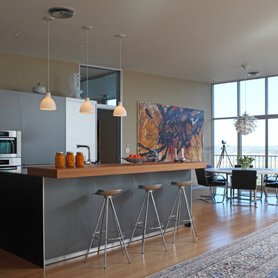 Open concept kitchen - contemporary open concept kitchen idea in Austin with wood countertops, flat-panel cabinets, gray cabinets and stainless steel appliances