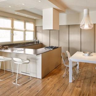 Ispirazione per una cucina minimal con ante lisce, ante beige, lavello sottopiano, pavimento in legno massello medio, penisola, pavimento marrone, top in marmo, paraspruzzi nero, paraspruzzi in marmo, elettrodomestici in acciaio inossidabile e top nero