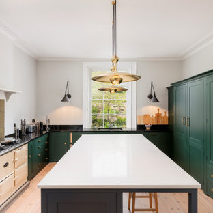 На фото: п-образная кухня в стиле современная классика с врезной раковиной, фасадами в стиле шейкер, зелеными фасадами, серым фартуком, цветной техникой, светлым паркетным полом, островом и черной столешницей с